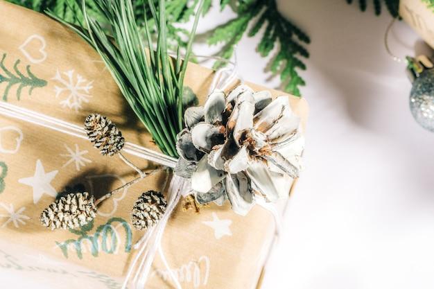 Regali di natale con confezione regalo decorata con pigne e ramoscelli su sfondo bianco, preparazione per le vacanze. regali di natale e capodanno. fatto a mano. messa a fuoco selettiva,