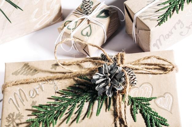 Regali di natale con confezione regalo decorata con pigne e ramoscelli su sfondo bianco, preparazione per le vacanze. messa a fuoco selettiva.
