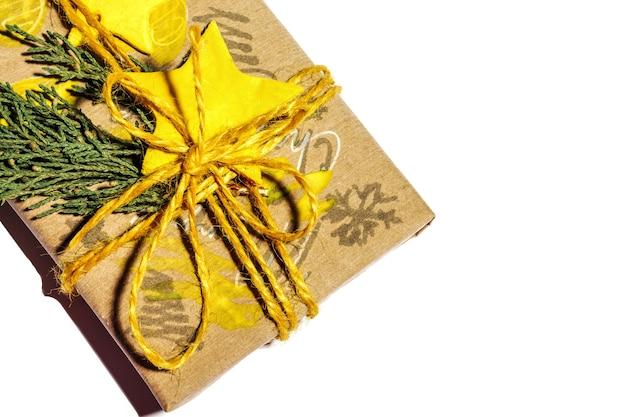 Regali di natale con scatola regalo decorata con stella gialla e ramoscelli isolati su sfondo bianco, preparazione per le vacanze. regali di natale e capodanno. fatto a mano. messa a fuoco selettiva.