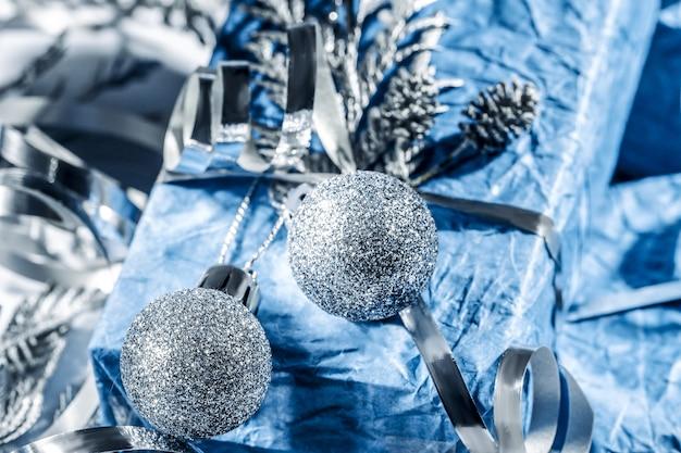 Regali di natale con confezione regalo in colore blu argento decorato con pigne e ramoscelli su sfondo bianco, preparazione per le vacanze. regali di natale e capodanno. fatto a mano. messa a fuoco selettiva.