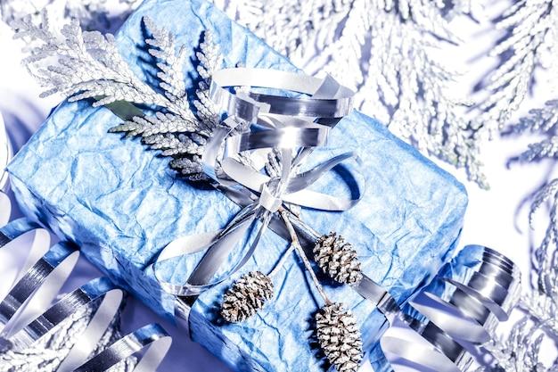 Regali di natale con confezione regalo in colore blu argento decorato con pigne e ramoscelli su sfondo bianco, preparazione per le vacanze. messa a fuoco selettiva.