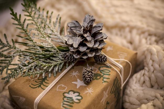 Regali di natale con confezione regalo artigianale decorata con pigne e ramoscelli su uno sfondo di tessuto di cotone, preparazione per le vacanze. regali di natale e capodanno. messa a fuoco selettiva,
