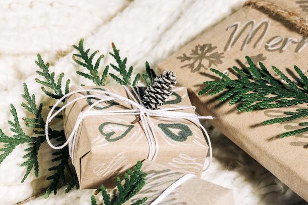 Regali di natale con confezione regalo fatta a mano decorata con pigne e ramoscelli su sfondo bianco, preparazione per le vacanze.