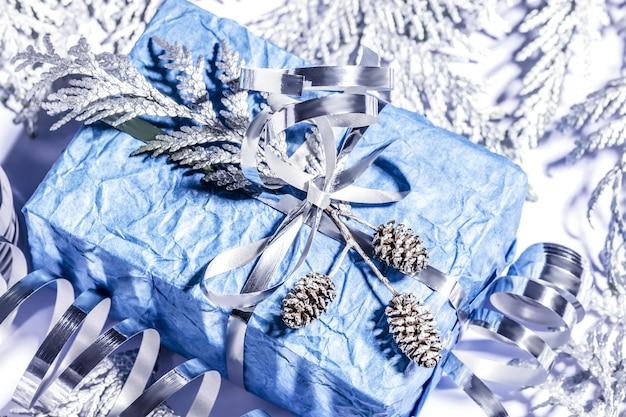 Regali di natale con confezione regalo fatta a mano in colore blu argento decorato con pigne e ramoscelli su sfondo bianco, preparazione per le vacanze. messa a fuoco selettiva.