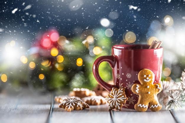 Punch di natale in una tazza rossa con cannella di panpepato e decorazioni natalizie.
