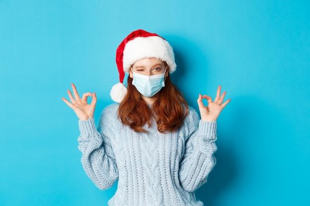 Natale, quarantena e concetto covid-19. carina ragazza rossa adolescente con cappello e maglione da babbo natale, che indossa la maschera per il viso del coronavirus, mostra segni ok, approva e loda qualcosa.
