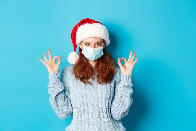 Concetto di natale, quarantena e covid-19. carina ragazza rossa con cappello da babbo natale e maglione, con indosso una maschera da coronavirus, che mostra segni ok, approva e loda qualcosa