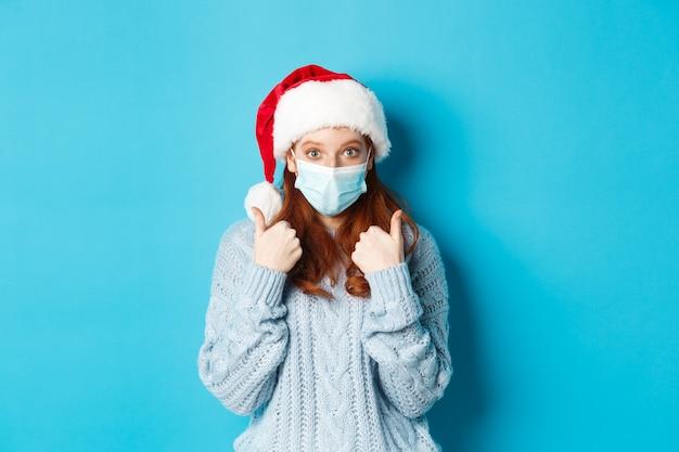 Concetto di natale, quarantena e covid-19. carina ragazza rossa con cappello da babbo natale e maglione, con indosso una maschera da coronavirus, che mostra i pollici in su, in piedi su sfondo blu