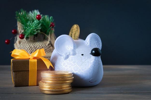 Salvadanaio del ratto di natale con regali e denaro. messa a fuoco selettiva. la cartolina del concetto di celebrare il natale e il nuovo anno.