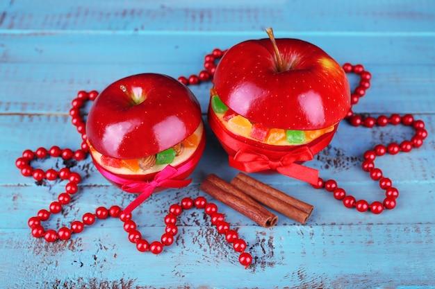 Mele rosse di natale ripiene di frutta secca su un tavolo di legno colorato