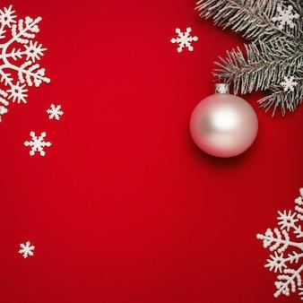Sfondo rosso di natale con abete, palla bianca e fiocchi di neve.