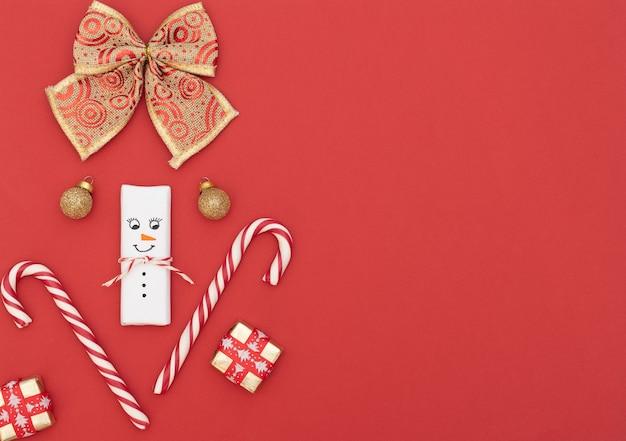 Sfondo rosso di natale con pupazzo di neve, bastoncini di zucchero, scatole regalo con nastro rosso, palline d'oro e fiocco d'oro. stile piatto laici con spazio di copia.
