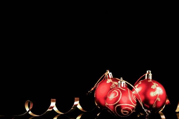 Palla di natale rossa con nastro d'oro su sfondo nero. biglietto per decorazioni natalizie