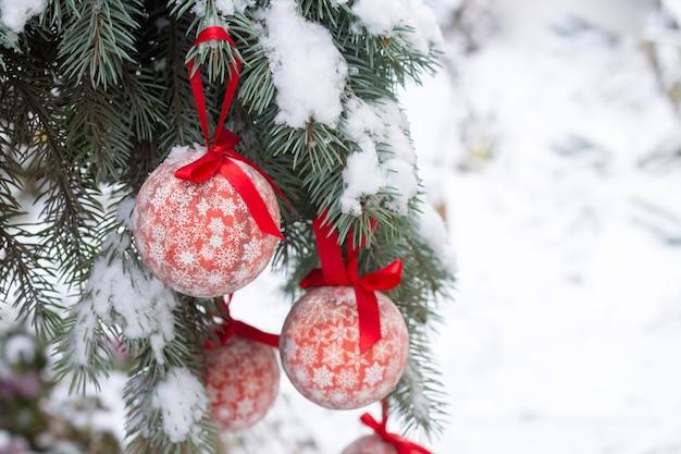 Palle rosse di natale che appendono sul ramo di albero con la neve