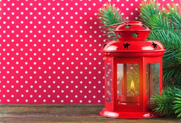 Lanterna di candela rossa di natale e albero di natale su sfondo rosso a pois.