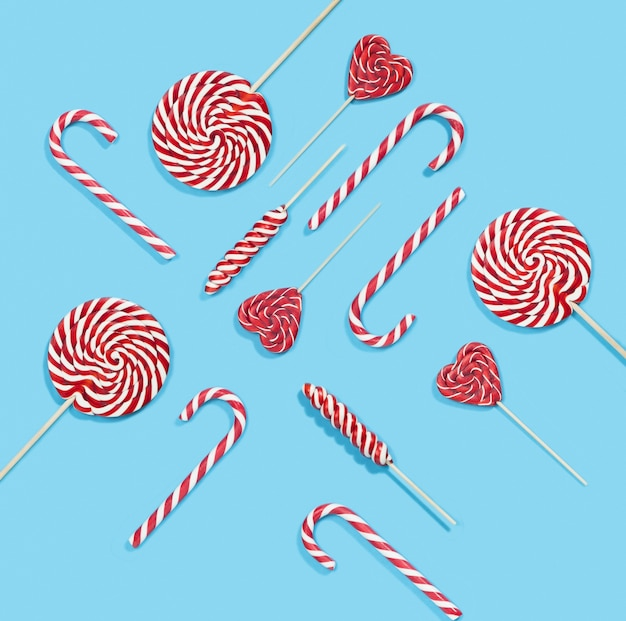 Modello di bastoncini di zucchero e lecca-lecca di natale rosso su sfondo blu
