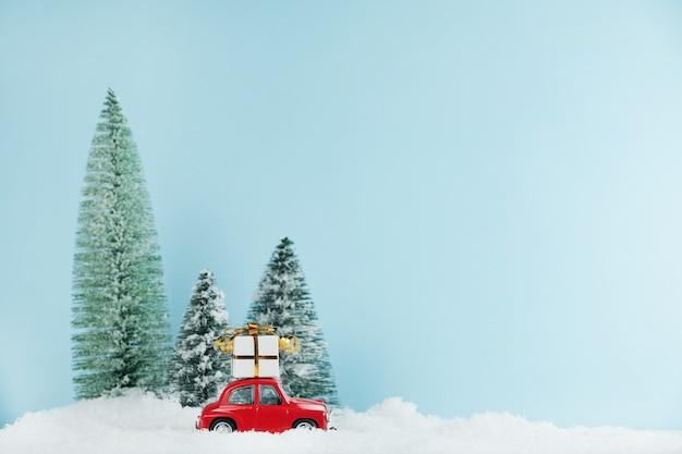 Automobile rossa di natale con una confezione regalo in una pineta innevata. carta di felice anno nuovo