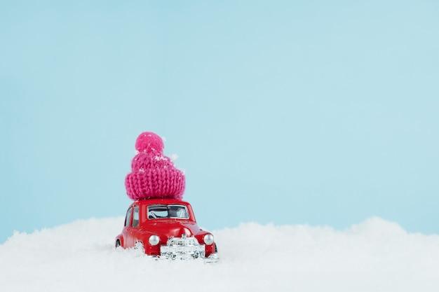 Automobile rossa di natale con cappello rosa lavorato a maglia in un paesaggio innevato. spazio per il testo. felice anno nuovo