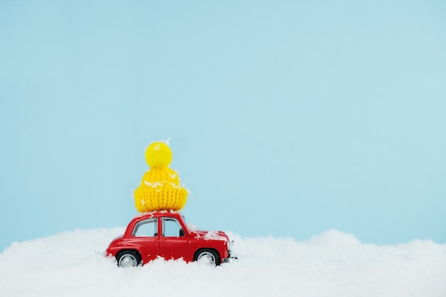 Automobile rossa di natale con cappello giallo lavorato a maglia in un paesaggio innevato. carta di felice anno nuovo