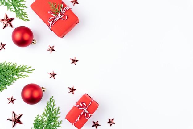 Contenitore di regalo rosso di natale con rami di abete rosso, bacche rosse su sfondo bianco.