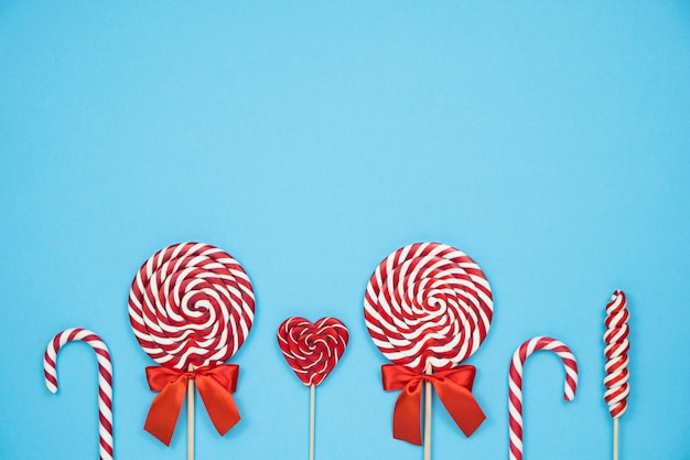 Bastoncini di zucchero a strisce rosse di natale e lecca-lecca su sfondo blu
