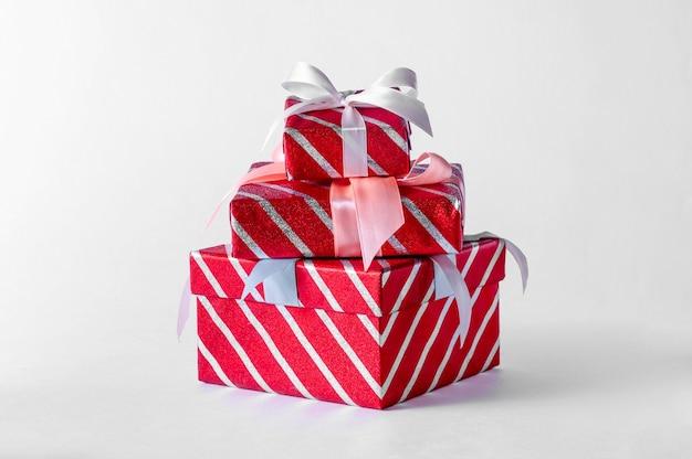 Scatole regalo a strisce rosse di natale su spazio luminoso. composizione minima creativa.