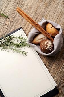 Appunti del menu del ristorante di natale con lo spazio della copia per testo. appunti di carta in bianco con ramo di albero di natale e pane sul fondo della tavola in legno