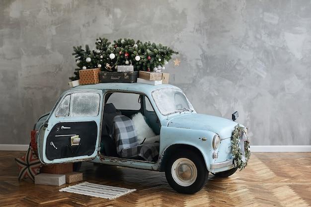 Retro automobile di natale decorata caricata con albero di natale e regali