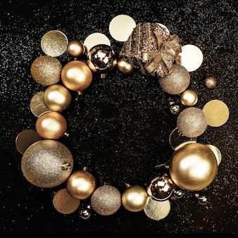 Cornice rotonda di natale di palline di ornamenti scintillanti d'oro su sfondo scuro