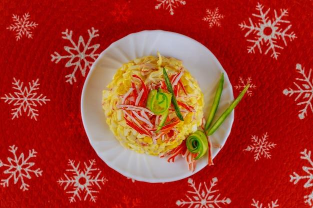 Insalata di natale a base di polpa di granchio, uova e mais in un piatto bianco. piatto di frutti di mare.