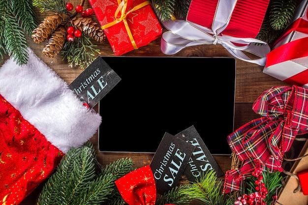 Concetto di vendita di natale. sfondo nero venerdì, verde o cyber monday con laptop, tablet, decorazioni natalizie e scatole regalo,