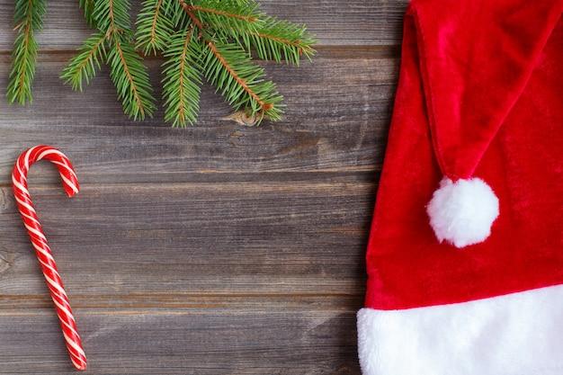 Cappello di babbo natale di natale con pompon, bastoncino di zucchero, ramo di abete rosso dell'albero di capodanno su un tavolo in legno rustico