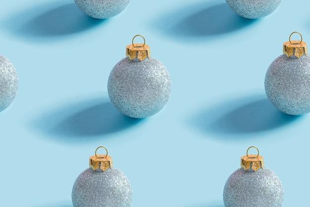 Reticolo senza giunte di natale da palline lucide blu su un blu pastello
