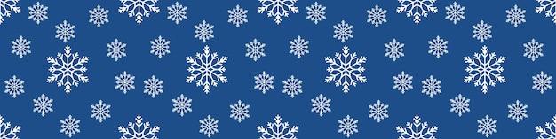 Reticolo senza giunte di natale con i fiocchi di neve su sfondo blu pastello. sfondo banner extra largo