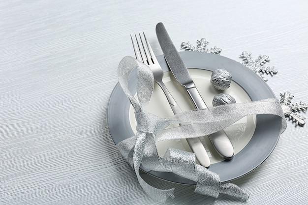 Posate da portata natalizie su piatto su tavolo in legno chiaro, primo piano
