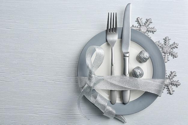Posate da portata natalizie sul piatto sopra un tavolo in legno chiaro