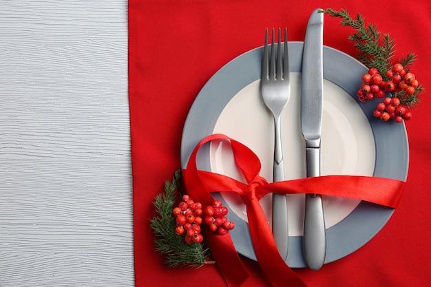 Posate da portata natalizie su piatto e tovagliolo su tavolo in legno chiaro, primo piano