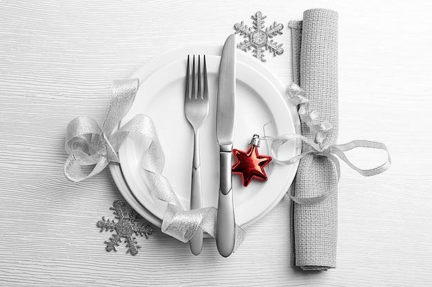 Posate da portata di natale sul piatto e tovagliolo sul tavolo in legno chiaro
