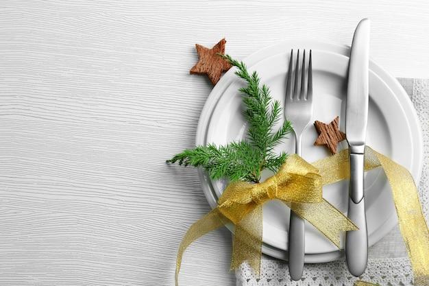 Posate da portata natalizie su piatto e tovagliolo su tavolo in legno chiaro