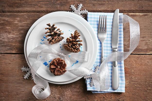 Posate da portata natalizie con tovagliolo e piatto su fondo in legno