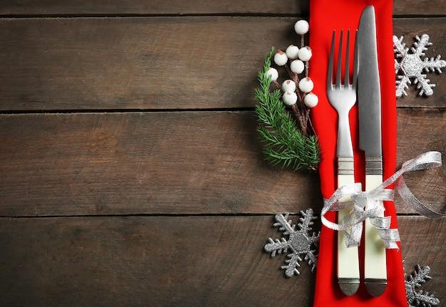Posate da portata natalizie con tovagliolo su fondo in legno