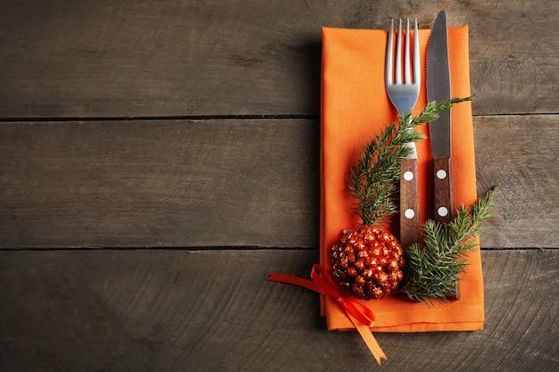 Posate da portata natalizie con tovagliolo su un tavolo di legno