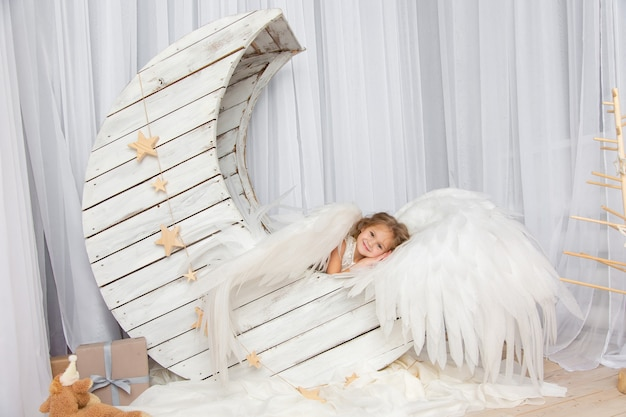 Riprese di natale di una bambina carina in studio con le ali