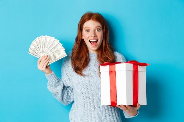 Natale e concetto di acquisto. donna rossa felice che tiene soldi e grande regalo di natale, mostrando dollari e regalo, sorridendo compiaciuto, in piedi su sfondo blu.