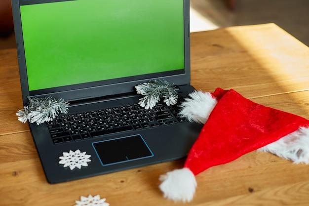 Concetto di shopping online di natale, computer portatile con schermo verde posizionato sul tavolo con regali decorati di natale, vista dall'alto della scrivania con computer portatile, scatole regalo