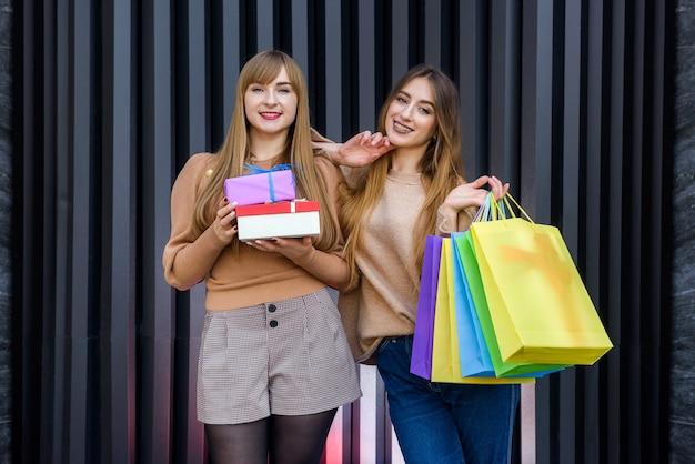 Shopping natalizio. due donne felici con sacchetti regalo colorati in posa dopo lo shopping