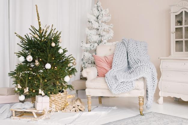 Slitta di natale con doni e una coperta, una sedia con cuscini vicino all'albero di natale in soggiorno, addobbata per il nuovo anno