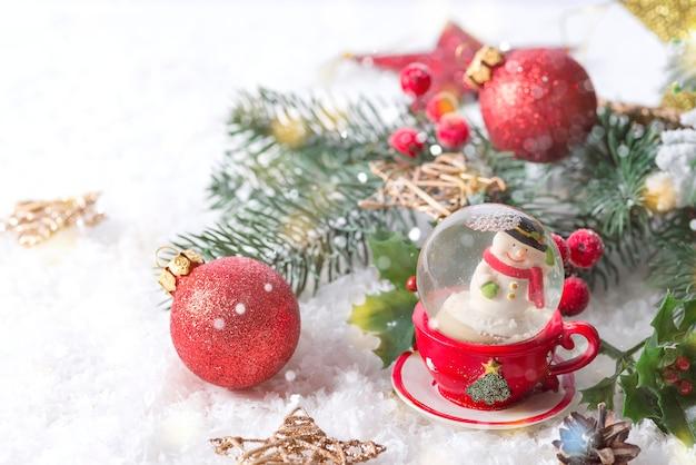 Globo di neve di natale con rami di pino e decorazioni festive sul tavolo della neve. concetto di natale o capodanno