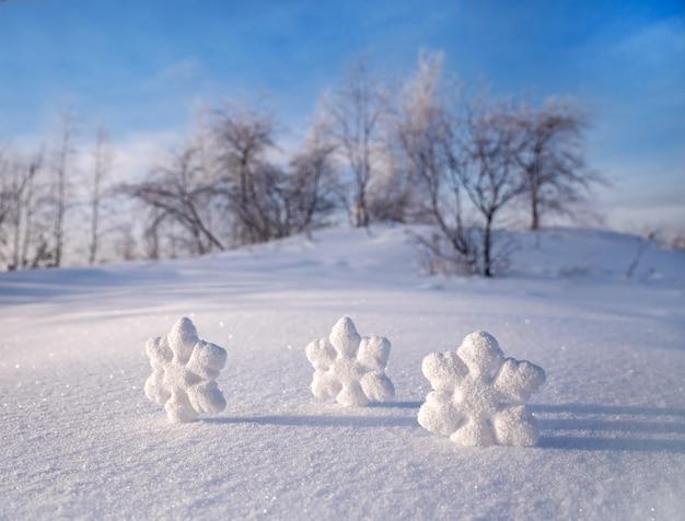 Fiocchi di neve di natale sulla neve bianca sullo sfondo degli alberi. giornata di sole gelido inverno.