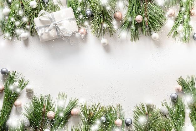 Cornice innevata di natale con regalo bianco, palline d'argento, rami sempreverdi su bianco.